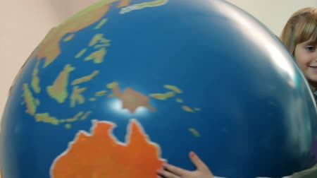 Kids playing with Earth globe Stock Footage
