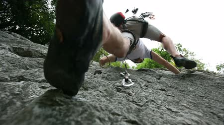 terreno extremo : HD1080p: Young man rock climbing in nature shot from below