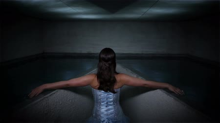 význam : Woman in a beautiful dress touching water surface and creating pattern reflectin on ceiling Dostupné videozáznamy
