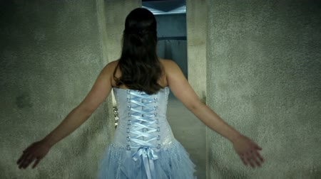 poça de água : Woman in a beautiful blue dress dancing toward water at the end of corridor