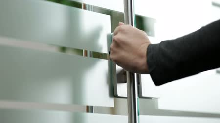 Woman opening glass door to office
