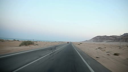 kahire : Driving on empty road by the sea in desert Stok Video