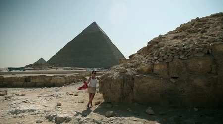 prehistory : Woman posing in front of pyramid Stock Footage