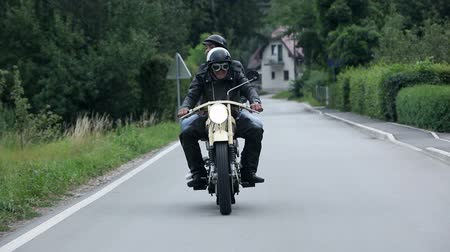 motocykl : Man and woman on retro motorcycle speeding on street