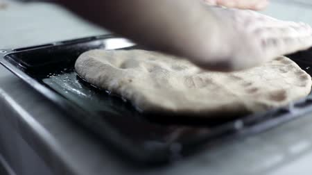 keksz : Close up shot of a black baking sheet and man is putting on dough and arranging it around the baking sheet Stock mozgókép