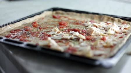 alaplap : Close up shot of a black baking sheet with dough and a person who is putting on different kinds of ingredients for pizza