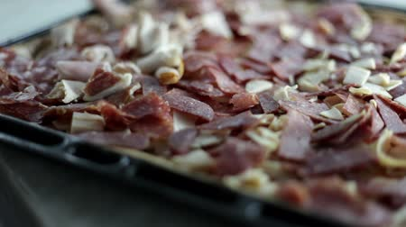 kiełbasa : Close up shot of a black baking sheet with dough and a person who is putting on different kinds of ingredients for pizza