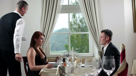 vacsora : Young couple having romantic lunch inside beautifull restaurant with fancy plate settings and wine