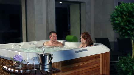 джакузи : young couple relaxing in jacuzzi with champagne and candels in front