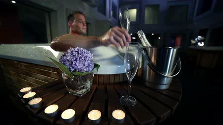 джакузи : night of wooden jacuzzi outside of fancy spcenter that is decorated with big purple flowers