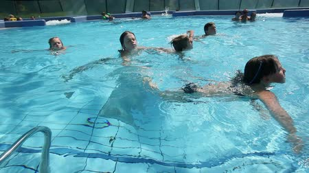 plavat : Close up of young kids swimming in outside pool crane shot