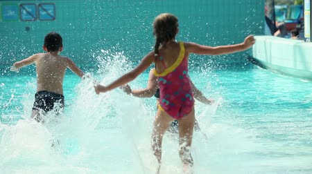 капелька : Close up on two girls and boy running into pool water