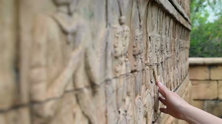 maia : Close up on woman hand touching wall art in ancient city