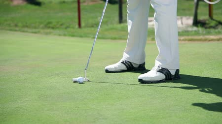 golfe : Close up shot on a golf course when a golfer hits white golf ball directly to the hall