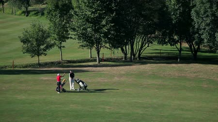 поле для гольфа : Slide shot of a couple that come on the golf course and starts preparing for playing golf