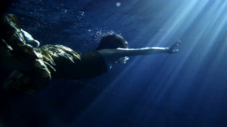 mergulhador : underwater activity and woman swimming under water in clothes