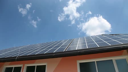 image house : Solar panels on a roof with clouds in the back