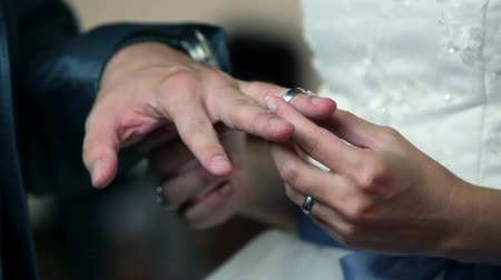 ring : bride and groom hand exchanging gold wedding rings on a wedding ceremony