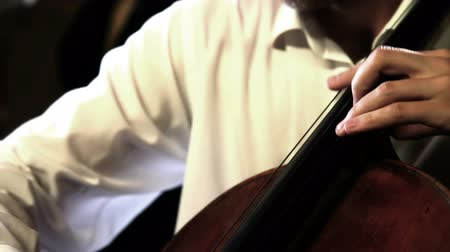 Close up pan shot of a cello player