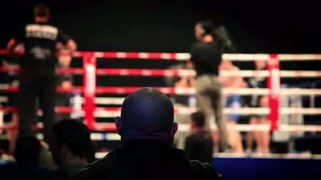 oluyor : Shot of audience watching fight in ring