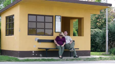 ül : Couple sitting on bench in front of orange house