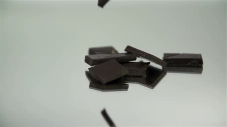biała czekolada : Pieces of chocolate are falling down on the reflective ground in slow motion