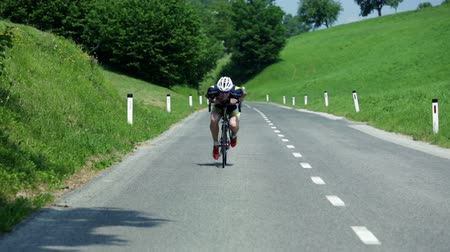 cyclists : VRHNIKA, SLOVENIA - AUG 24, 2013: Cyclist is gaining speed in his aerodynamic pose in downhill ride Stock Footage
