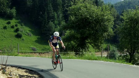 cyclists : VRHNIKA, SLOVENIA - AUG 24, 2013: Sole cyclist is showing his uphill riding skills on sunny day Stock Footage