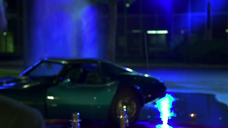 firemen : Shot of a man standing in front of blue Corvette with spurting hydrant