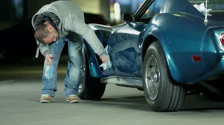 antika : Man carefully polishing the side part of Corvette car