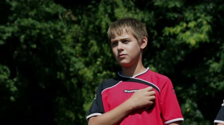 sport dzieci : Young footballers listening to the nationa anthem on in the middle of the field