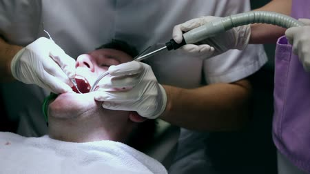 dentysta : Dentist during his work with help of assistant