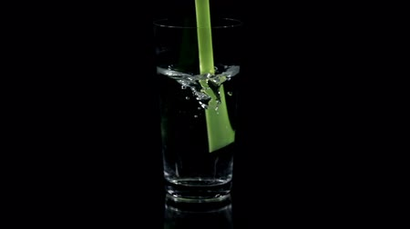 bebida : Stirring a drink with a green straw on black background Vídeos
