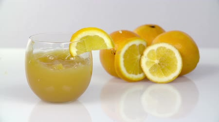 szorítás : Two pieces of fruit fall into glass with juice and citruses in the back