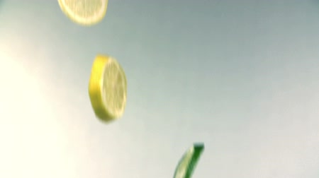 calcário : Slices of lemon and lime fall to white surface in slow motion Stock Footage