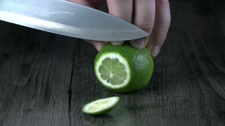 cutting up : Cutting up a lime with kitchen knife on wooden-like tablecloth Stock Footage