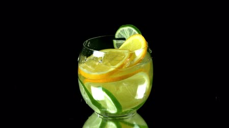 coquetel : Pieces of citrus fall into glass of water with lime and lemon slices