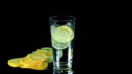 calcário : Slices of lemon fall into glass of water in slow motion