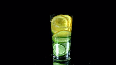 limonada : Peces of citrus fall into water on black background and spill some water