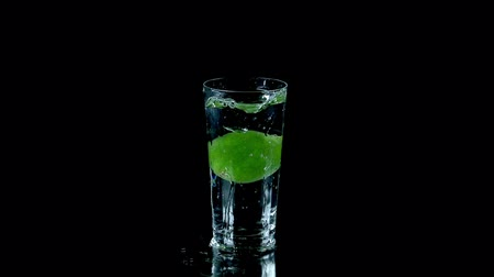 calcário : Whole lime falls into glass of water on black background Stock Footage