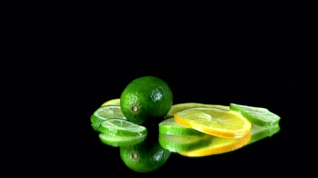 calcário : Whole lime falls onto pile of citrus slices on the table Stock Footage