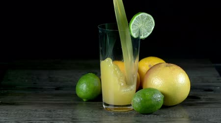 lemoniada : Juice puring into glass in the front of exotic fruit