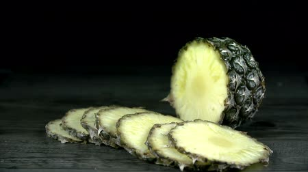 ananas : Pineapple slices fall on black table in slow motion Stok Video