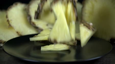 ananas : Pineapple pieces fall onto black plate in slow motion Stok Video