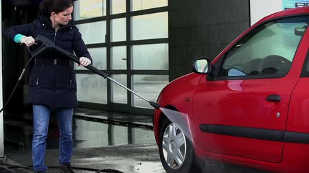 lavagem : Female cleaning her car with water pressure in slow motion Vídeos