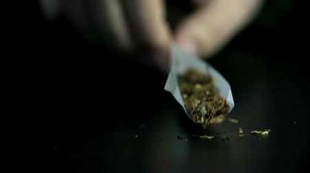 taciz : Picking up a rolling paper with filter, tobacco and marihuana
