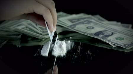 cheirando : Female making some cocaine lines with credit card with money bills in the back