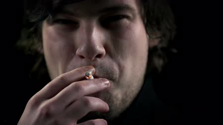 dospělý : Young man inhales a cigarette smoke in slow motion