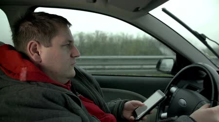 řídit : Driver texting during the drive on a highway shot in slow motion