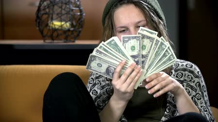 pontos : Teenager with a lot of one dollar bills in her hands